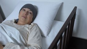 Hopeless female patient suffering cancer lying in sickbed and looking at camera. Stock footage stock video footage