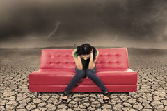 Hopeless female on red sofa at dry ground. Picture of stress female  on red sofa with dry soil under bad weather Royalty Free Stock Image