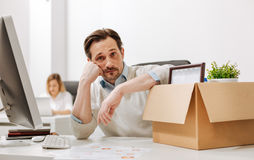 Hopeless fired office manager expressing sadness in the office. Need a help . Fired sorrowful upset office manager sitting and holding the box with his stock images