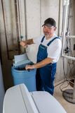 Hopeless home installer having trouble. Installing a new household water softener giving a thumbs down gesture with a rueful smile Stock Image