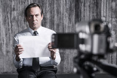 Hopeless hostage. Frustrated businessman caught by a criminal sitting in front of a dirty wall and holding paper while video camera filming it on the foreground Royalty Free Stock Photos