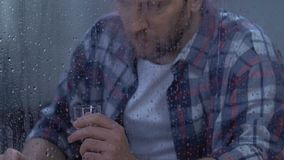 Hopeless middle-aged male drinking vodka suffering depression, alcohol addiction stock footage