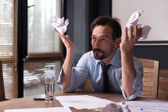 Hopeless miserable man holding crumpled paper Stock Photography