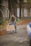 Hopeless old tramp with cart and board with sign need money. Stock Photography