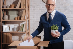 Hopeless professional clearing his workplace. Where do I go from here. Thoughtful concerned elderly businessman putting away his things after being fired while royalty free stock images