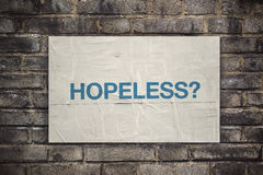 Hopeless on Rustic Poster Paper on Brick Wall Royalty Free Stock Photography