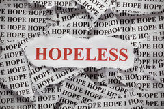 Hopeless. Torn pieces of paper with the word Hope and word Hopeless in red color. Concept Image. Close-up Stock Images