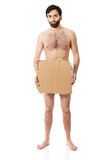 Hopeless undressed man with a piece of cardboard. Royalty Free Stock Photography