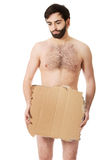 Hopeless undressed man with a piece of cardboard. Royalty Free Stock Photos