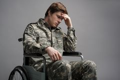Upset disabled soldier feeling helpless. Hopeless young military man sitting in wheelchair. He is looking down with frustrated look and propping his head with Stock Photos