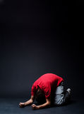 Hopelessness. Desperate man praying in darkness stock photography