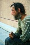 Sad homeless man. Homeless poor beggar in depression sitting on the sidewalk stock images