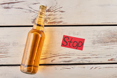 Hopelessness is not reason to drink. Bottle of lager, old wooden table Royalty Free Stock Photos