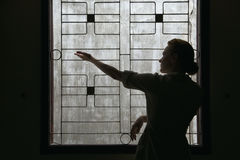 Hopelessness. Silhouette of a girl standing in front of an open window, the wall behind him stock images