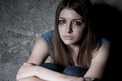 Hopelessness. Top view of young woman crying and looking at camera while sitting against dark wall Royalty Free Stock Photos