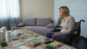 Hopeloze hogere die vrouw in rolstoel gevoel van medische behandeling op lange termijn wordt vermoeid stock footage