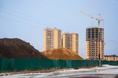 Hopen van zwarte humusrijke aarde en zand achter omheining op bouwterrein Royalty-vrije Stock Foto's