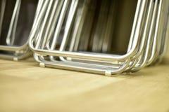 Hopfällbara metallstolar som göras av rör som i rad staplas Arkivfoto