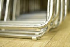 Hopfällbara metallstolar som göras av rör som i rad staplas Fotografering för Bildbyråer