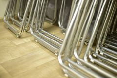 Hopfällbara metallstolar som göras av rör som i rad staplas Arkivfoton