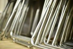 Hopfällbara metallstolar som göras av rör som i rad staplas Royaltyfri Foto