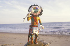 Hopi Kachina doll holding objects on beach with ocean in the background Royalty Free Stock Images