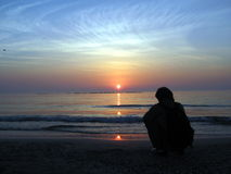 Hoping. Young man watching the sun Stock Image
