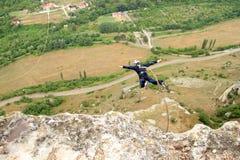 Hopp av en klippa med ett rep Royaltyfri Fotografi