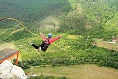 Hopp av en klippa med ett rep Arkivfoto