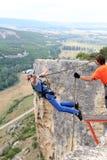 Hopp av en klippa med ett rep Arkivfoton