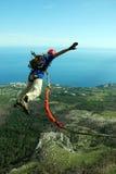 Hopp av en klippa med ett rep Upphetsad liten flicka Fotografering för Bildbyråer
