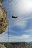 Hopp av en klippa med ett rep Upphetsad liten flicka Arkivfoto