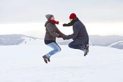 Hopp för snö för vinter för berg för parmankvinna Fotografering för Bildbyråer