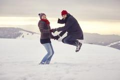 Hopp för snö för vinter för berg för parmankvinna Royaltyfri Foto