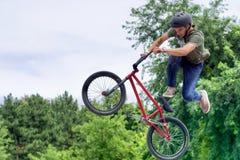Hopp för tonårs- cyklist för BMX-fristil farligt Arkivfoton