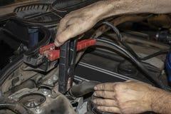 Hoppa batteriet av ett stannat medel - händer av repairmanen som fäster klämmor till batteristolpar under hoodwithnedgångsidor arkivfoton