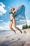 Hoppa den lyckliga flickan på stranden, sportig sund sexig kropp för passform i bikini Arkivbilder
