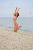 Hoppa den lyckliga flickan på stranden, sportig sund sexig kropp för passform i bikini Fotografering för Bildbyråer