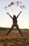 Hoppa den tonårs- flickan som kastar sidor upp i luften Royaltyfri Fotografi