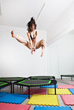 Hoppa den unga kvinnan på en trampolin Arkivbilder