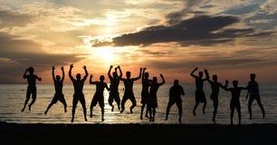 Hoppa för glädje på stranden royaltyfria foton