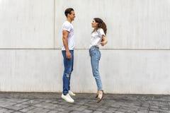 Hoppa för lyckliga par för sidosikt förälskat mot den gråa väggen royaltyfria bilder