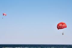 Hoppa fallskärm på havet Arkivbild