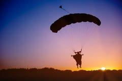 hoppa fallskärm silhouetteskydiveren under Arkivbilder