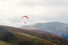Hoppa fallskärm skydiverflyget i moln på berg, loppadventu royaltyfri foto