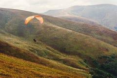 Hoppa fallskärm skydiverflyget i moln på berg, loppadventu royaltyfri fotografi