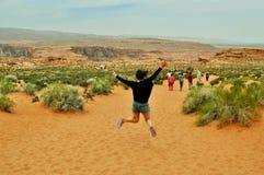 Hoppa kvinnlign i kanjonen för Nationalpark arroundhästsko, Utah royaltyfria bilder