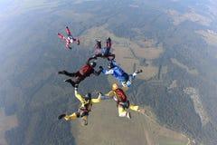 Hoppa med fritt fall för bildande En grupp av skydivers gör ett sekventiellt i himlen royaltyfria bilder