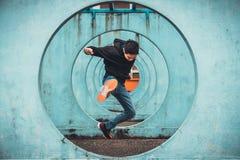 Hoppa och sparkande handling för ung asiatisk aktiv man, cirkel som kretsar väggbakgrund Extremt sportaktivitetsbegrepp arkivfoton