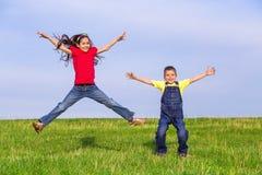 Hoppa ungar på grönt fält Arkivfoto